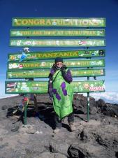 Michele fly's the JHMT flag at the summit of the highest free standing mountain in the world!
